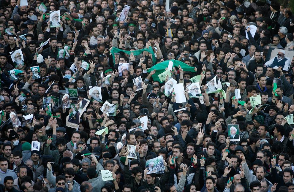4. Иранцы держат фотографии и зеленые плакаты на похоронах Великого аятоллы Хусейна Али Монтазери в Куме 21 декабря 2009 года. (AP Photo)