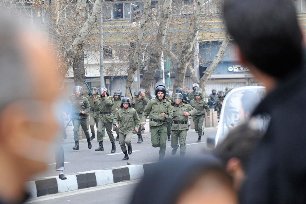 7. Иранские полицейские бегут к демонстрантам-оппозиционеры в центре Тегерана 27 декабря 2009 года. (REUTERS/Stringer)