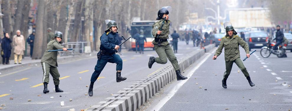 8. Штурмовой отряд иранской полиции с камнями и дубинками бегут за демонстрантами во время антиправительственного протеста в Тегеране 27 декабря 2009 года. (AP Photo)