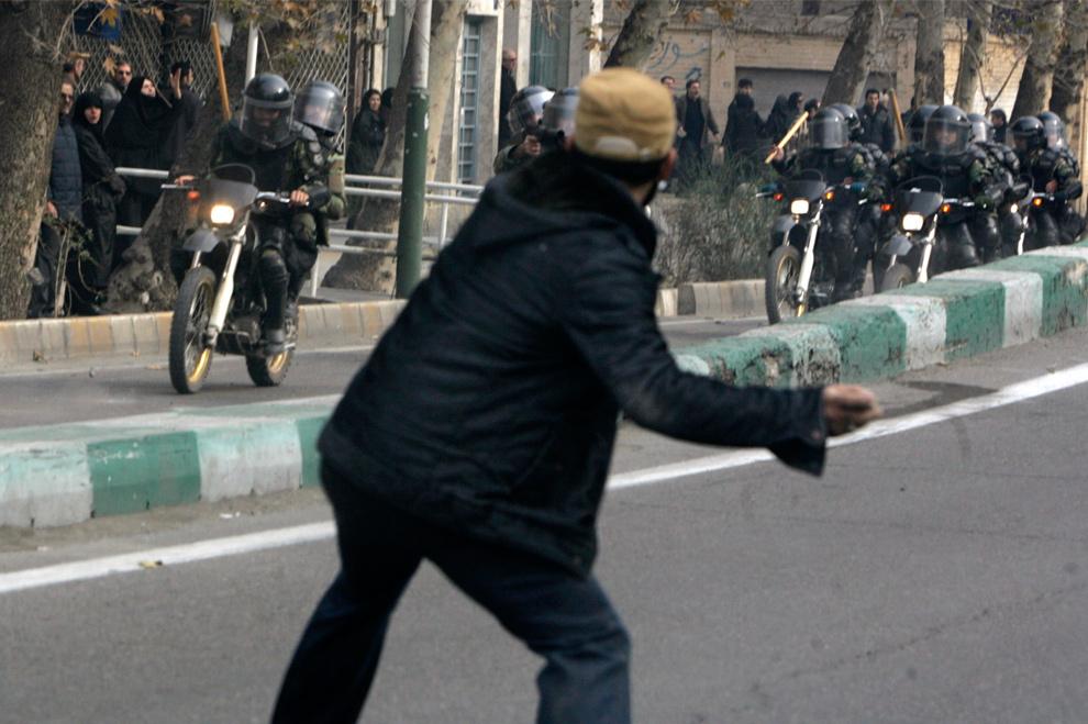 9. Демонстрант бросает камень в полицейских во время яростных столкновений в центре Тегерана 27 декабря 2009 года. (REUTERS/Stringer)