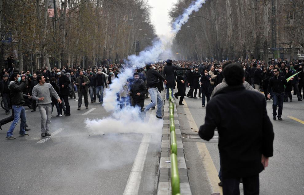 10. Иранские оппозиционеры бросают жестянки со слезоточивым газом обратно в полицейских в Тегеране 27 декабря 2009 года. (AFP/Getty Images)