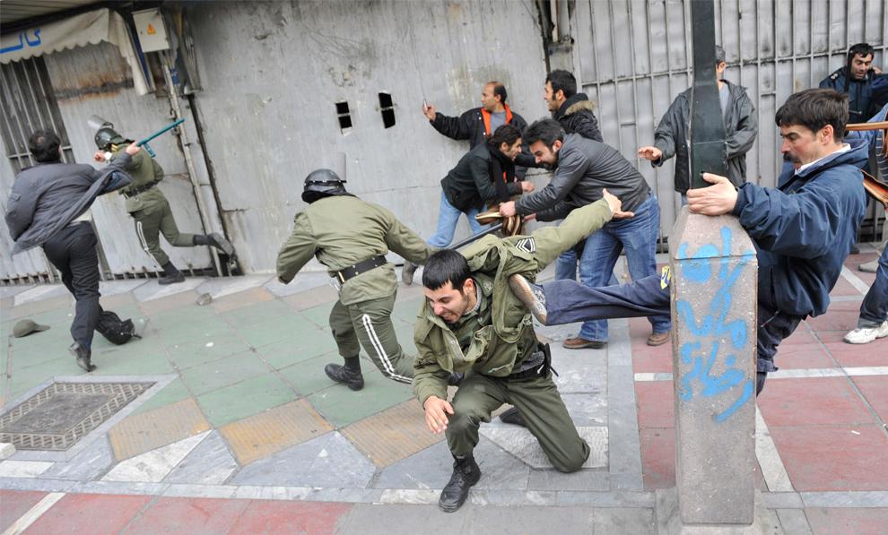 12. Сторонники иранской оппозиции бьют полицейских во время конфликта в Тегеране 27 декабря 2009 года. (REUTERS/Stringer)