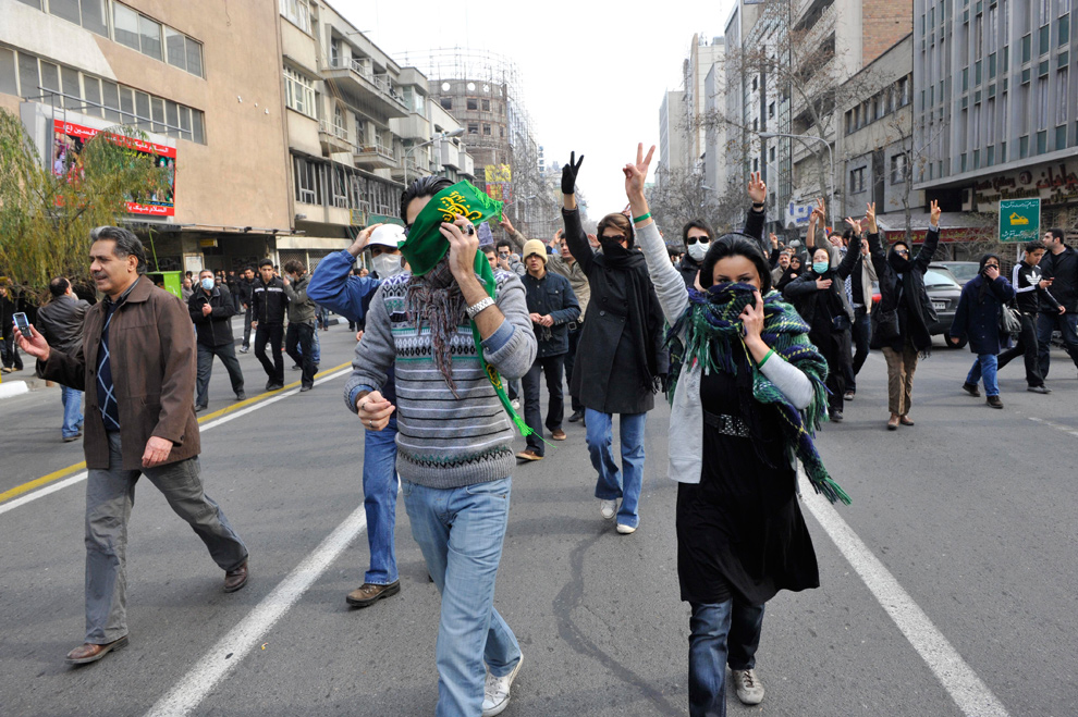 14. Иранские демонстранты показывают знак победы, прикрывая лица от полиции во время антиправительственных протестов в Тегеране 27 декабря 2009 года. (AP Photo)