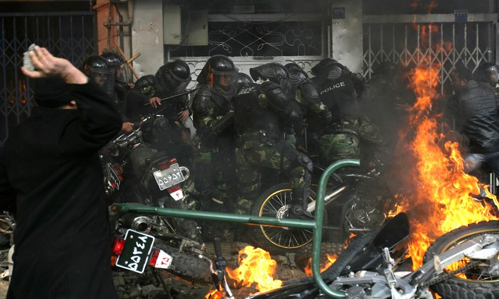 16. Иранский демонстрант замахивается камнем в полицию, окруженную у магазинов другими демонстрантами, на фоне горящих полицейских мотоциклов в Тегеране 27 декабря 2009 года. (AFP/Getty Images)