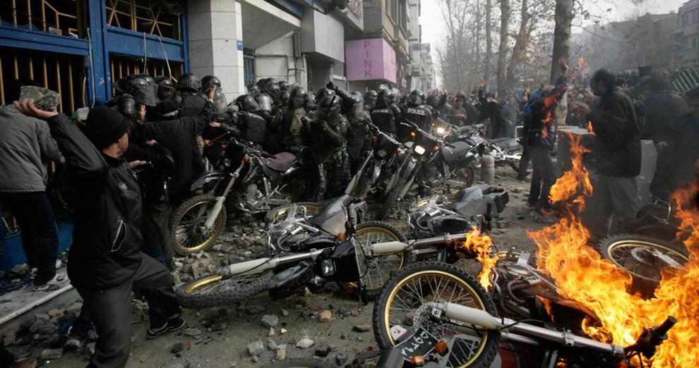 17. Демонстрант бросает камень в полицейских, пока другие демонстранты поджигают их мотоциклы во время конфликта в Тегеране 27 декабря 2009 года. (REUTERS/Stringer)