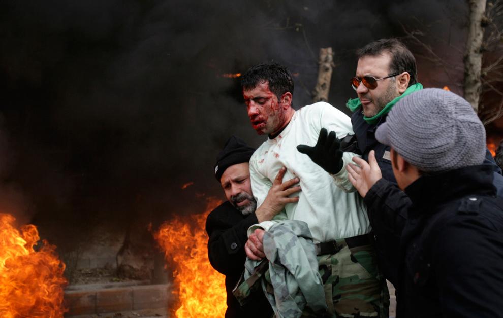 19. Иранские демонстранты уводят раненного полицейского в безопасное место, после того как он был избит другими демонстрантами в центре Тегерана 27 декабря 2009 года. (REUTERS/Stringer)