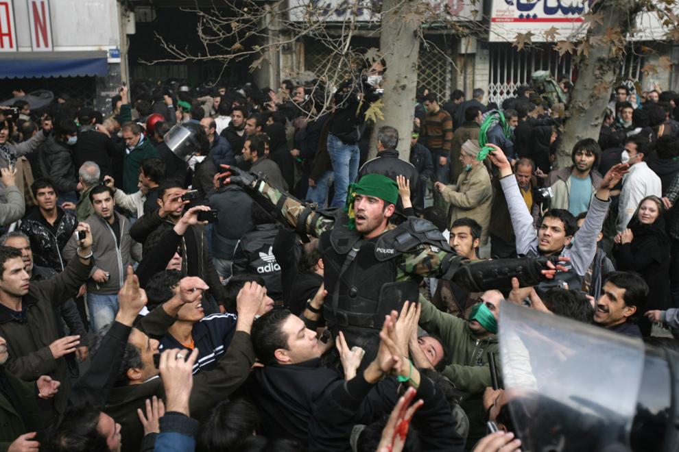 21. Демонстранты подняли в воздух иранского полицейского и повязали ему на голову зеленый платок – символ оппозиции – во время столкновений на улице Революции в Тегеране 27 декабря 2009 года. (AP Photo)