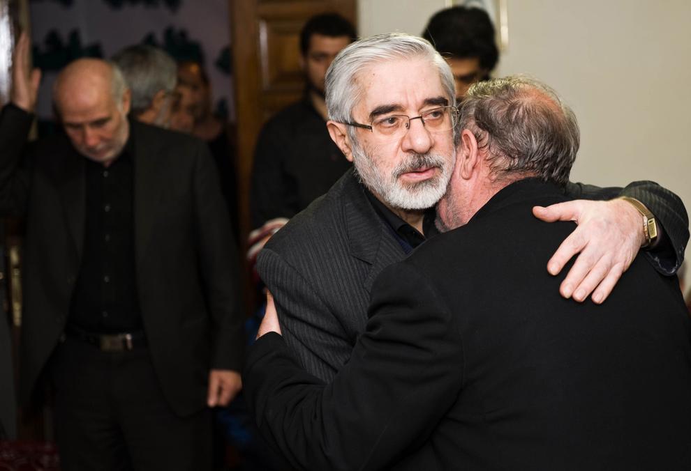 25. Лидер иранской оппозиции Мир Хусейн Мусав (в центре) принимает соболезнования по случаю гибели его племянника Сейеда Али Хабиби-Мусави в Тегеране. 35-летний племянник Мира Хусейна Мусави Сейед был застрелен в Тегеране во время протестов 27 декабря, превратившихся в кровавую бойню между оппозицией и полицией. 29 декабря иранская полиция сообщила, что «террорист» убил племянника лидера оппозиции Мира Хусейна Мусави во время инцидента, не имеющего отношения к правительственным мятежам. (Arash Ashourinia/AFP/Getty Images)