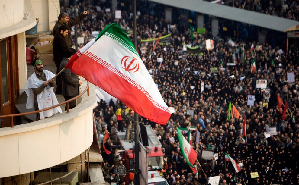 26. Сторонник иранского правительства машет флагом Ирана во время демонстрации против оппозиции во время праздника Ашура в Тегеране 30 декабря 2009 года. Демонстрация на площади Революции в Тегеране стала одной из нескольких главных мятежей в крупных иранских городах, возникших в результате ответа клириков, семинарских школ и вооруженных сил на оппозиционные протесты против президента Махмуда Ахмадинеджада. (REUTERS/Morteza Nikoubazl)