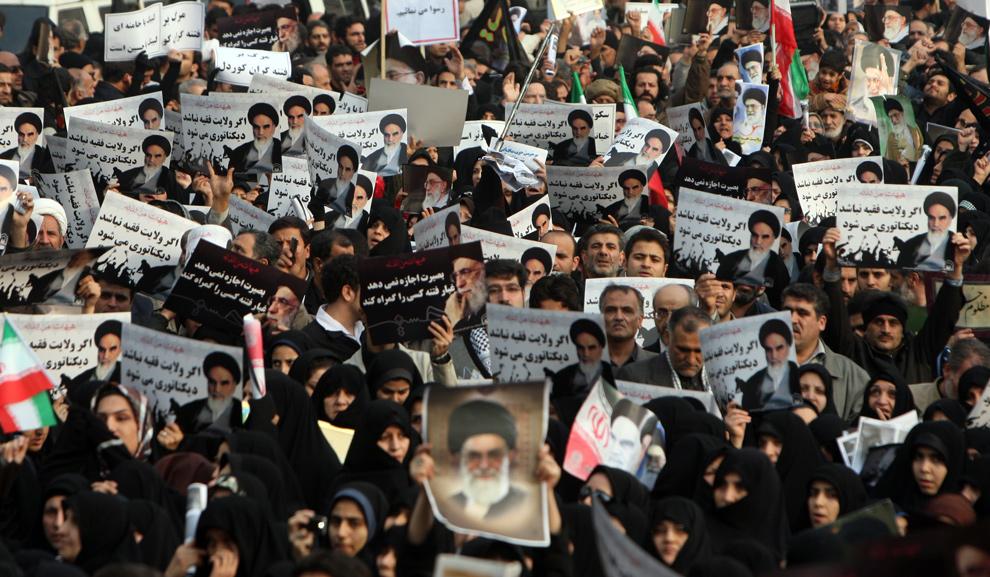 29. Большая толпа сторонником иранского режима вышла на улицы Тегерана 30 декабря 2009 года, чтобы выразить протест против оппозиции, которую они обвинили в том, что они «пешки врагов». (ATTA KENARE/AFP/Getty Images)
