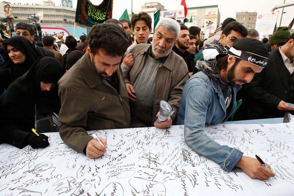 31. Иранские демонстранты подписывают послание судье, осуждая лидеров оппозиции во время правительственного митинга на площади Революции в Тегеране 30 декабря 2009 года. (AP Photo/Vahid Salemi)