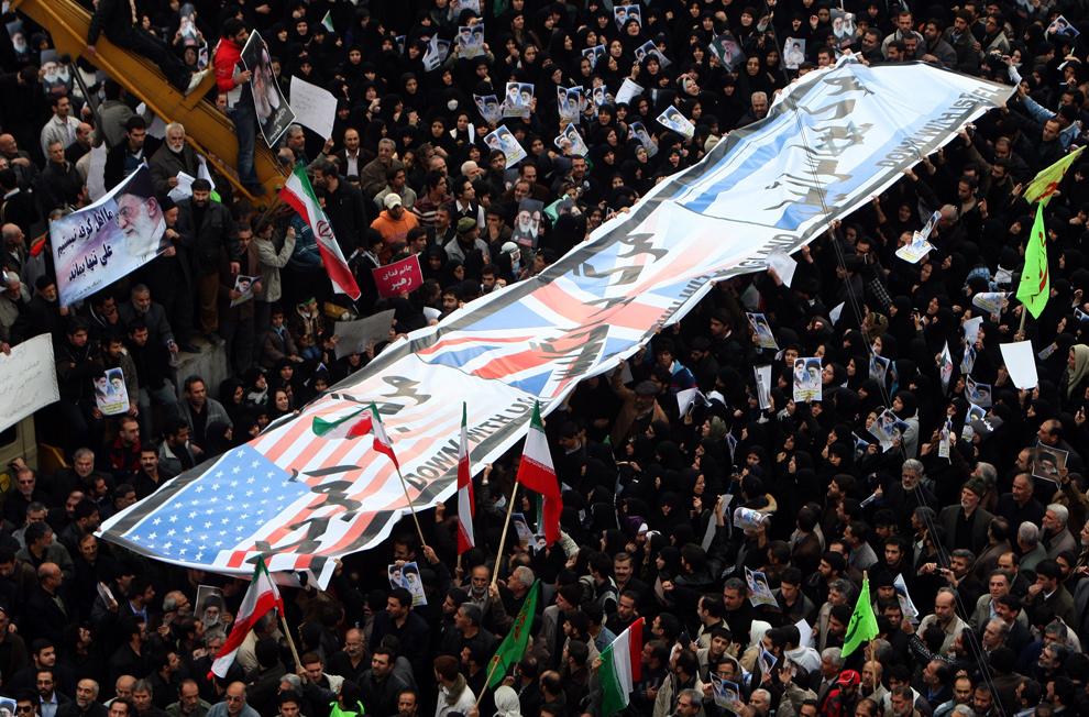 32. Сторонники иранского режима несут баннер из флагов США, Великобритании и Израиля на улицах Тегерана 30 декабря 2009 года. (ATTA KENARE/AFP/Getty Images)