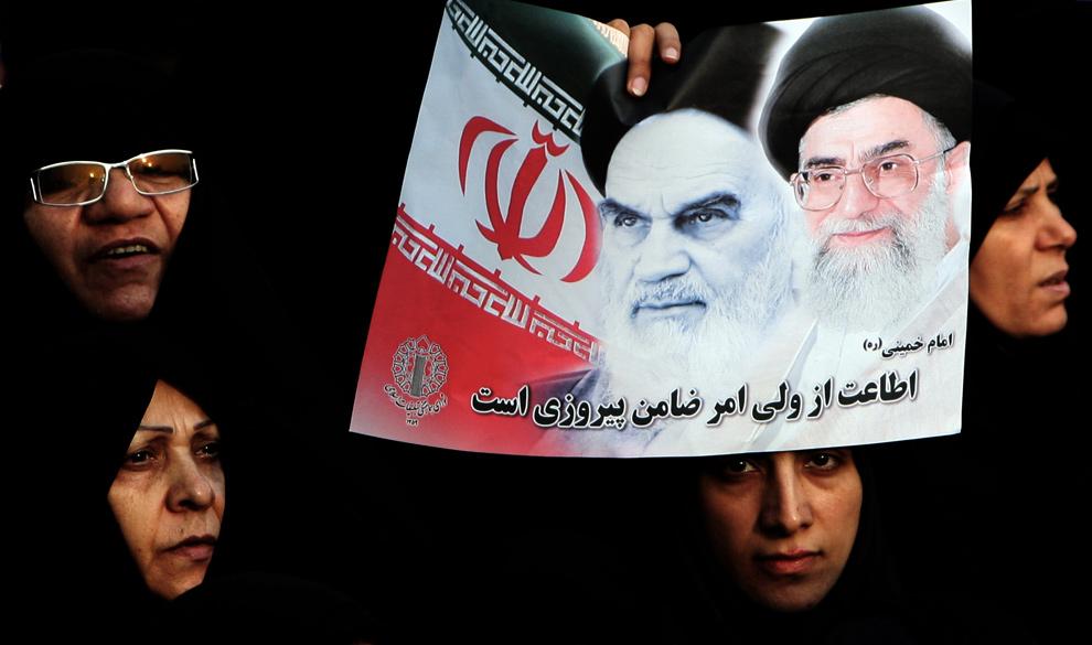 33. Женщины-сторонницы иранского режима держат портрет иранского верховного лидера Али Кхаменеи (справа) и основателя исламской республики Аятоллы Рухоллы Кхоменеи на улицах Тегерана 30 декабря 2009 года. (ATTA KENARE/AFP/Getty Images)