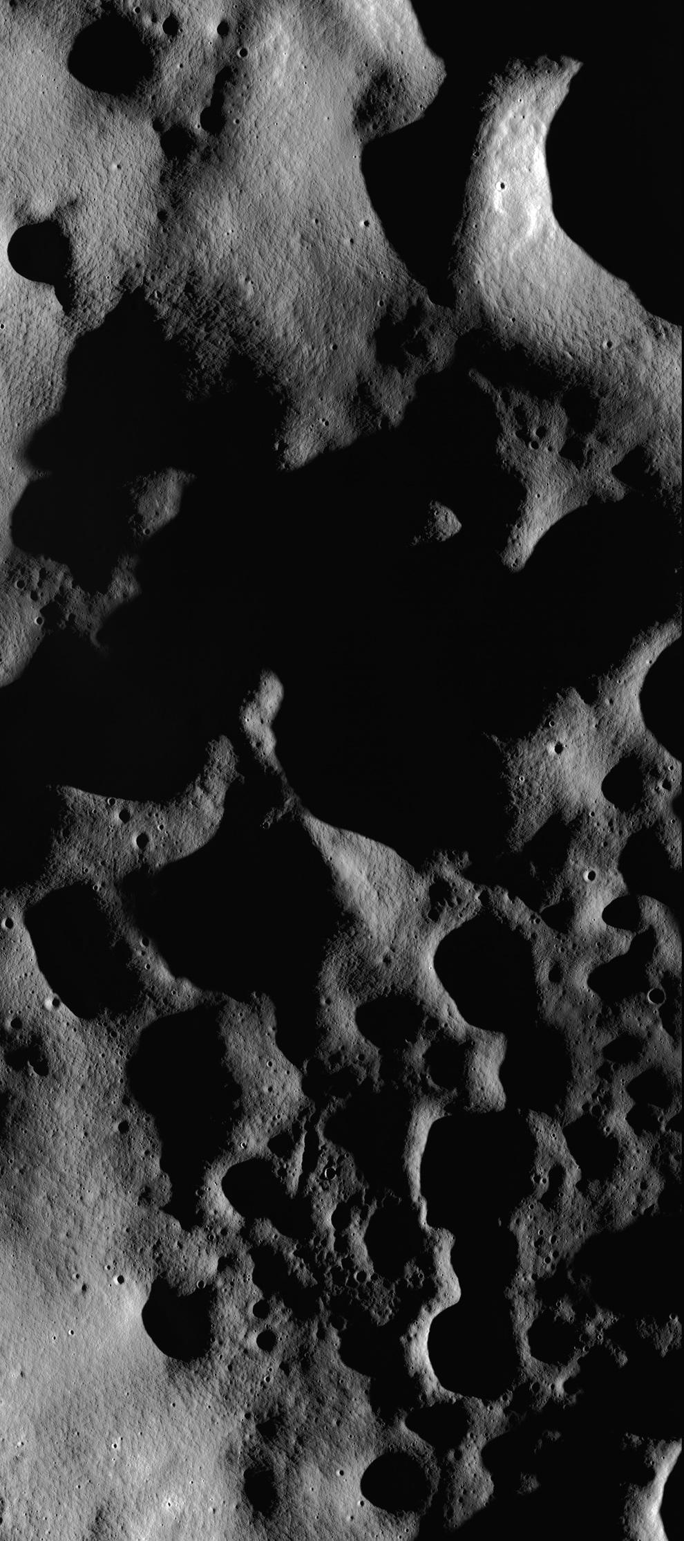 12. Часть огромного снимка восточного края кратера Рождественский В на восходе, демонстрирующая голый рельеф поверхности Луны, 4 июля 2009 года. (NASA/GSFC/Arizona State University)