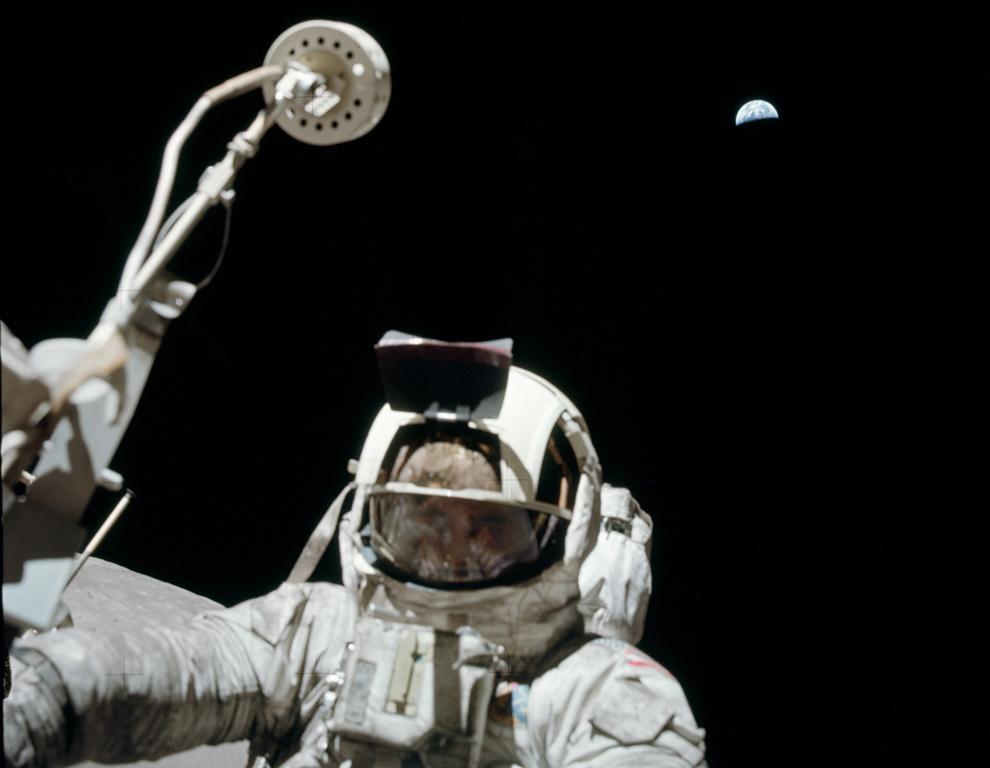 18. Астронавт Аполло 17 Харрисот Шмит смотрит в камеру на луноходе на фоне Земли 13 декабря 1972 года. (NASA)
