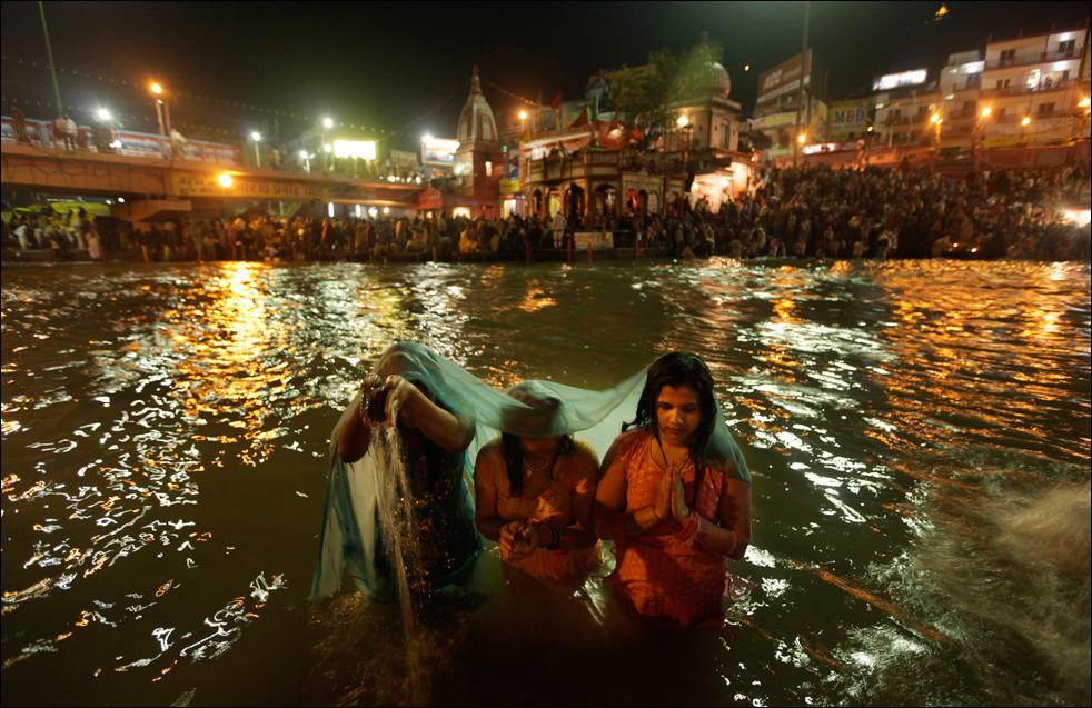 4. Семья молится во время купания в Ганге в первый день Кумбха Мела в Харидваре 14 января. (AP / Saurabh Das)