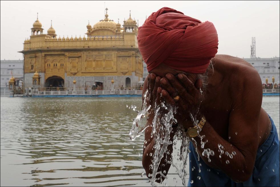 7. Индийский сикх умывается во время ритуального купания по случаю Магхи Мела у Золотого храма в Амритсаре 14 января. (AFP / Getty Images / Narinder Nanu)