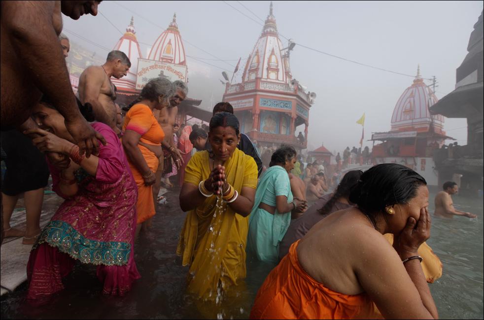 17. Люди купаются и молятся в благоприятный день фестиваля Кумбха Мела на берегу реки Ганг 15 января. (AP / Saurabh Das)