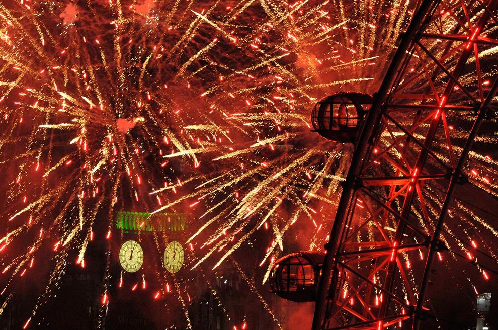 1. Фейерверк рядом с Лондонским глазом и зданием  Парламента на Темзе во время празднования Нового года в Лондоне 1 января 2010. (REUTERS/Toby Melville)