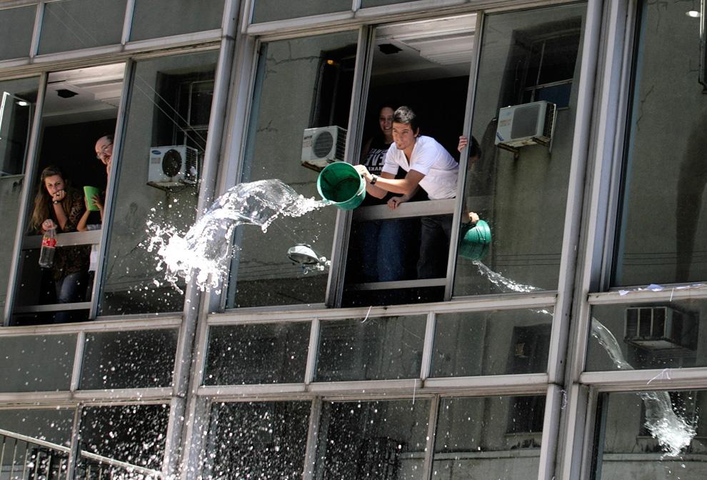 3. Рабочие выливают воду на людей во время празднования Нового Года в Монтевидео, Уругвай, 31 декабря 2009. В последний рабочий день года рабочие по традиции выливают воду на людей и выбрасывают старые календари. (REUTERS/Andres Stapff)