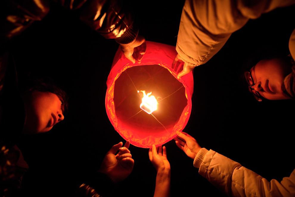 6. Жители Чэнду, провинция Сычуань, Китай, выпускают в небо фонарь с желаниями 31 декабря 2009 года. (AP Photo)