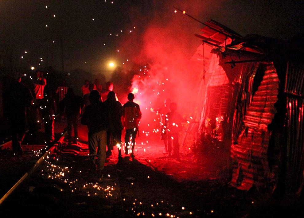 11. Молодежь празднует Новый Год фейерверками и петардами в трущобах Кибера в Найроби, Кения, 1 января 2010 года. (REUTERS/Noor Khamis)