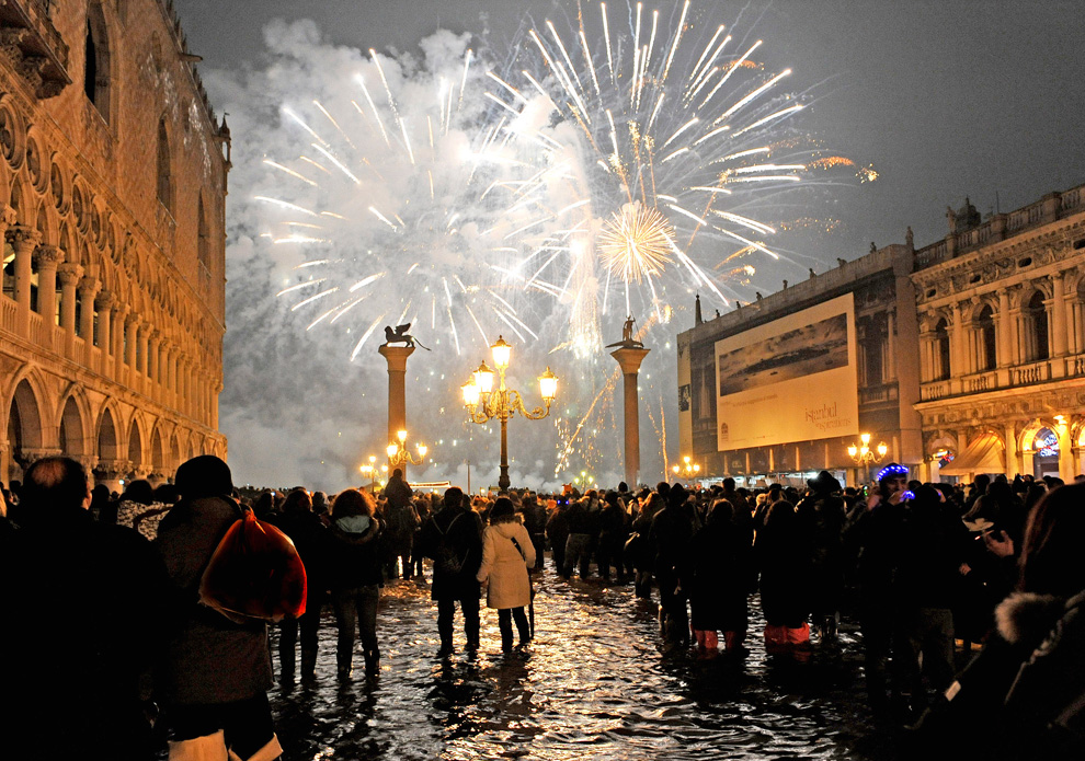 15. Люди смотрят на новогодний салют над площадью святого Марка в Венеции утром в пятницу 1 января 2010 года. (AP Photo/Luigi Costantini)
