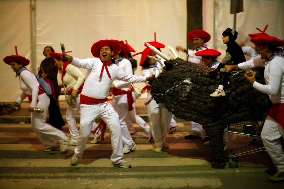 18. Люди в костюмах участников традиционных бегов с быками празднуют Новый год в Койне, недалеко от южного города Испании Малага утром 1 января 2010 года. (REUTERS/Jon Nazca)
