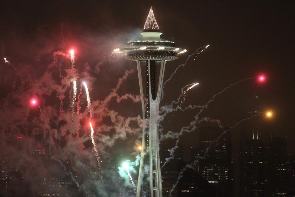 25. Салют из башни Space Needle освещает центр Сиэтла в честь встречи Нового года 1 января 2010 года. (AP Photo/The Seattle Times, Cliff DesPeaux)