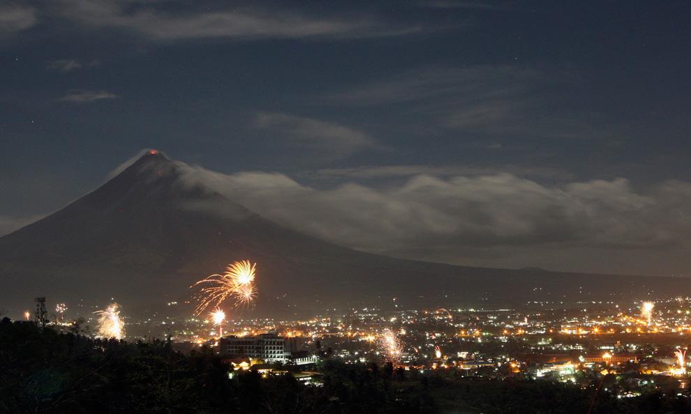 27. Салют освещает небо у вулкана Майон во время празднования Нового года в Легазпи, провинция Албай к югу от Манилы 1 января 2010 года. Вулкан Майон, известный своей почти идеальной конусной формой в регионе Бикол более двух недель извергал пепел, грязь и камни. (REUTERS/Romeo Ranoco)