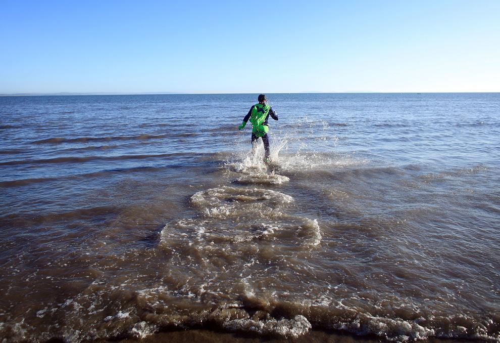32. Участник благотворительного заплыва «Саундерсфут» в честь Нового года бежит по ледяной воде 1 января 2010 года в Саундерсфуте недалеко от Тенби, Уэльс. Сотни смельчаков нырнули в ледяное море, чтобы встретить Новый год и собрать деньги для благотворительных организаций. (Christopher Furlong/Getty Images)