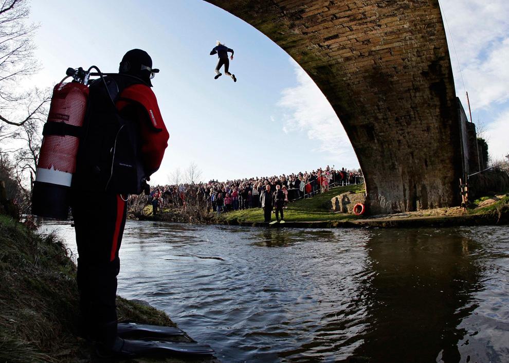 33. Дайвер-спасатель смотрит, как человек прыгает с моста в реку Дов во время традиционного благотворительного мероприятия в честь Нового года в Мэпплтоне, Англия, 1 января 2010 года. Команды плывут 800 метров по реке, а потом прыгают с моста в ледяные воды реки Дов. А затем участники бегут 457 метров до ближайшего паба. (REUTERS/Darren Staples)