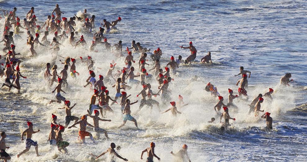 35. Люди бегут в воду во время традиционного новогоднего заплыва в Северном море в Гааге 1 января 2010 года. В этом году около 8000 человек приняли участие в заплыве – одном из 63, проходящих на территории Нидерландов. (ROBIN UTRECHT/AFP/Getty Images)