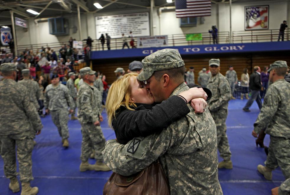 1. 23-летняя Натали Пикет (слева) целует своего мужа сержанта 23-летнего Пола Пикета 31 декабря, когда его отряд из второго батальона 87 пехотного полка вернулся в Форт Драм, Нью-Йорк, после года службы в Афганистане. Семья Пикетов из Миндена, штат Луизиана. (AP / David Goldman)