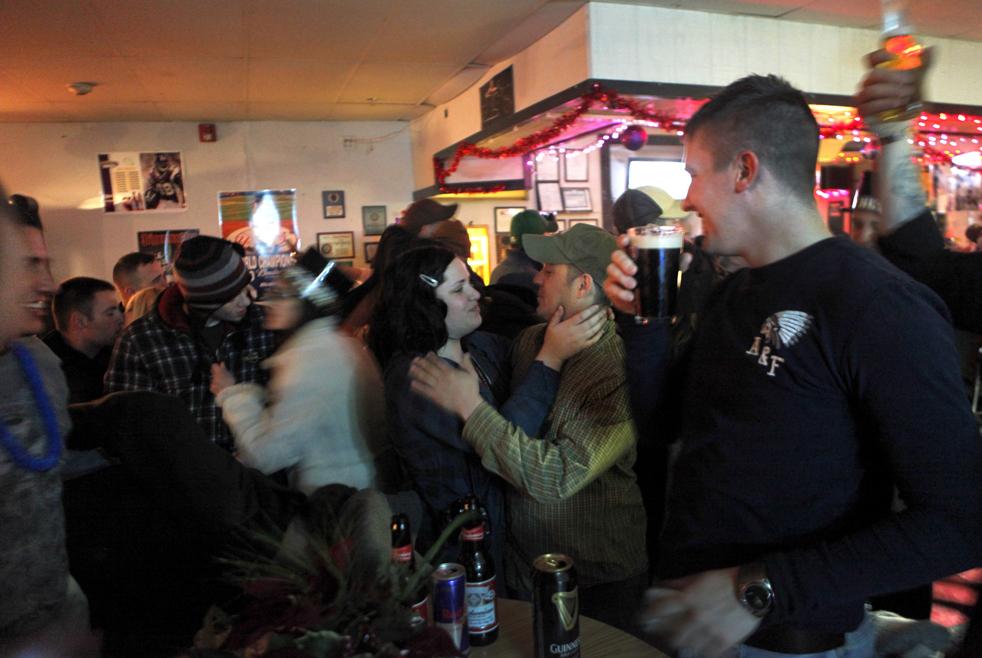 4. 26-летняя Оливия Нэммэк (в центре слева) обнимает своего мужа 28-летнего специалиста Дона Джонсона из второго взвода второго батальона в полночь в баре «Толстые мальчики» в Уотертауне, Нью-Йорк, 1 января во время празднования Нового Года в день возвращения взвода из Афганистана. (AP / David Goldman)