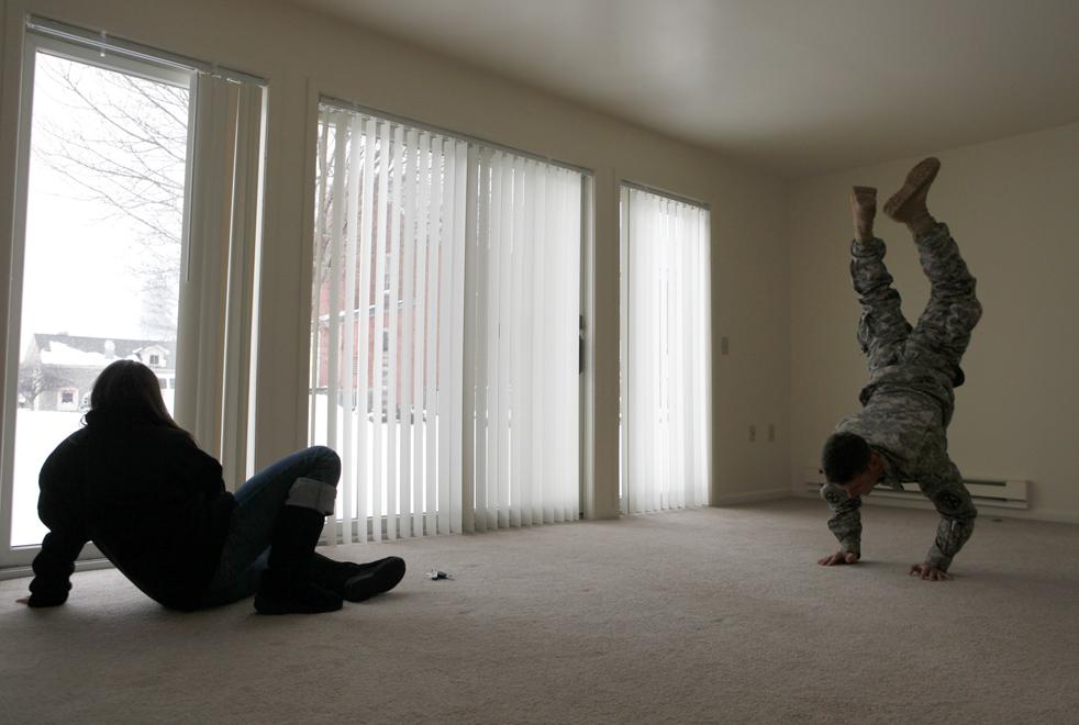 8. Старший лейтенант 24-летний Марк Хоган из второго взвода стоит на руках, пока они с его девушкой 24-летней Лиз Хэкер ждут прибытия вещей в их новую квартиру в Сакетс Харбор, Нью-Йорк, в день возвращения взвода Хогана после годовой службы из Афганистана. (AP / David Goldman)