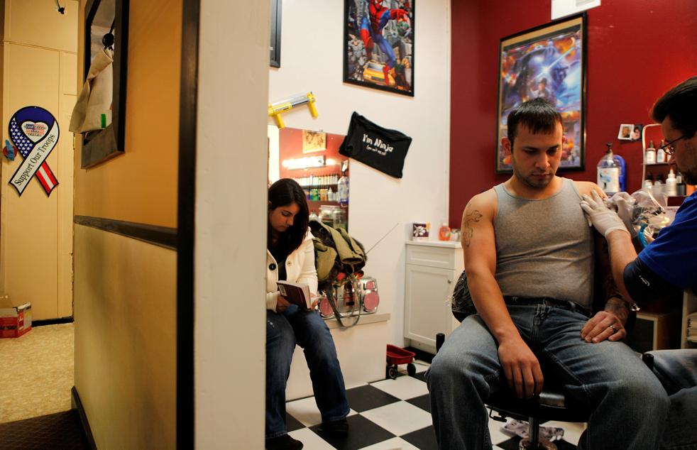 10. Специалист 23-летний Гэри Галланд (справа) из второго звода второго батальона 87-ого пехотного взвода делает себе татуировку в салоне «Empyre Tattoo» в Картедже, Нью-Йорк, 3 января. Галланд начал татуировку еще до того, как его забрали в Афганистан. Его жена 20-летняя Рианна Галланд сидит рядом. (AP / David Goldman)