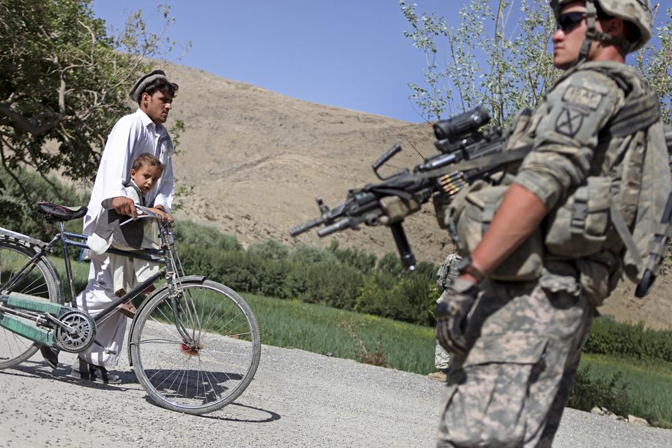 13. Мужчина с маленьким мальчиком проходят мимо рядового первого класса 22-летнего Майка Шмидта из Брунсвика, штат Мэн, во время его патрулирования в долине Танги в афганской провинции Вардак 16 августа 2009 года. (AP / David Goldman)