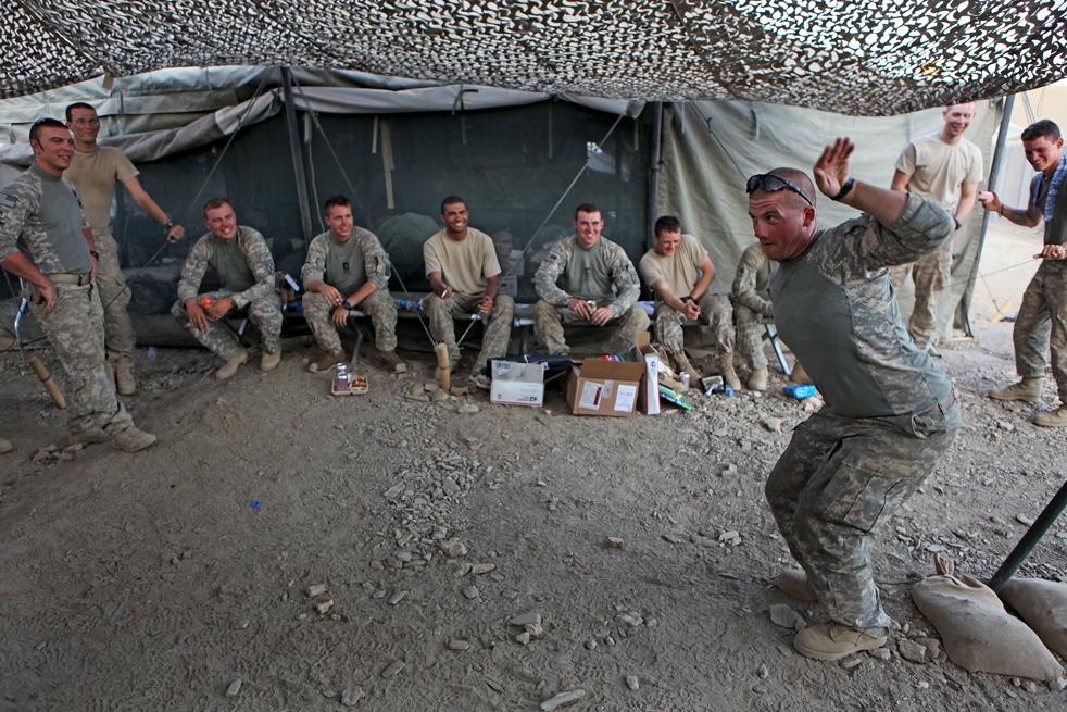 15. Рядовой Кейвен Кокс (справа) из второго взвода показывает пантомиму на песню «Я маленький чайник» перед своими товарищам в качестве наказания за ошибку во время последнего патрулирования на аванпосте Танги в афганской провинции Вардак 15 августа 2009 года. (AP / David Goldman)