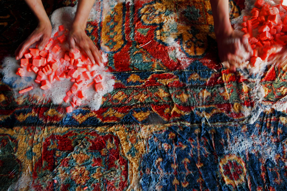 1. Афганские рабочие моют коврик осветляющей жидкостью, чтобы сгладить яркие цвета, на заводе по производству ковров 8 января в Кабуле. (Getty Images / Majid Saeedi)