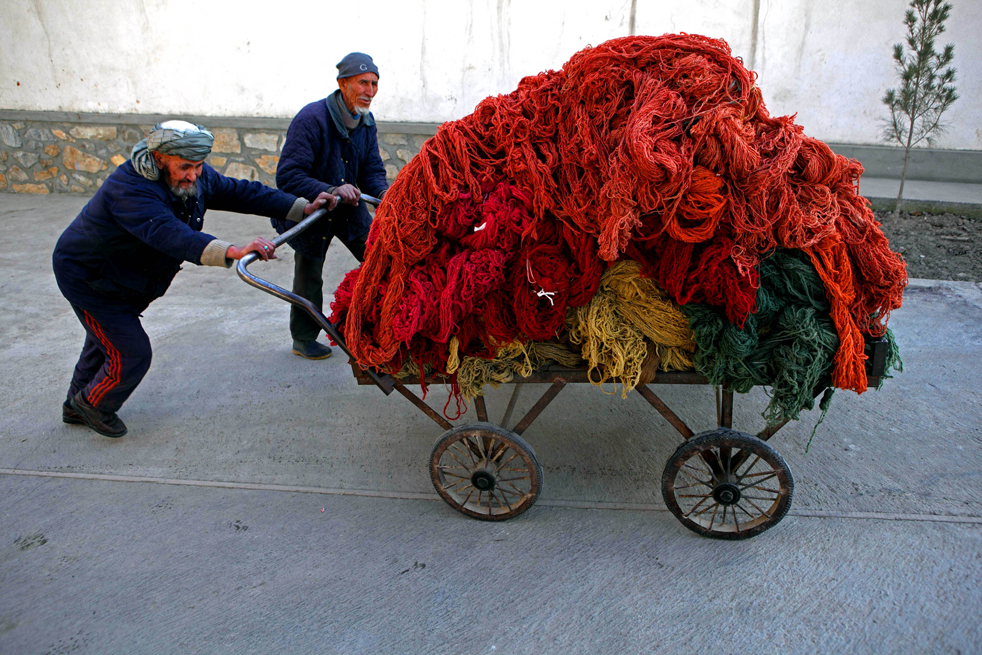 6. Афганские рабочие собирают нити после их покраски на заводе по производству ковров 9 января в Кабуле. (Getty Images / Majid Saeedi)