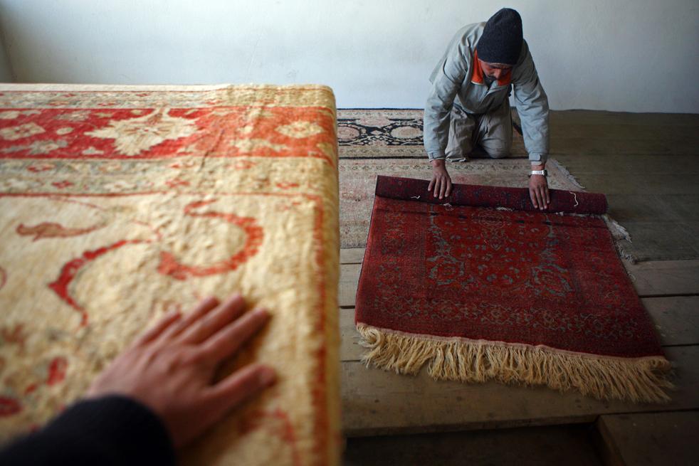 15. Афганский рабочий сворачивает ковер на заводе в Кабуле перед его отправлением для экспорта 9 января. (Getty Images / Majid Saeedi)