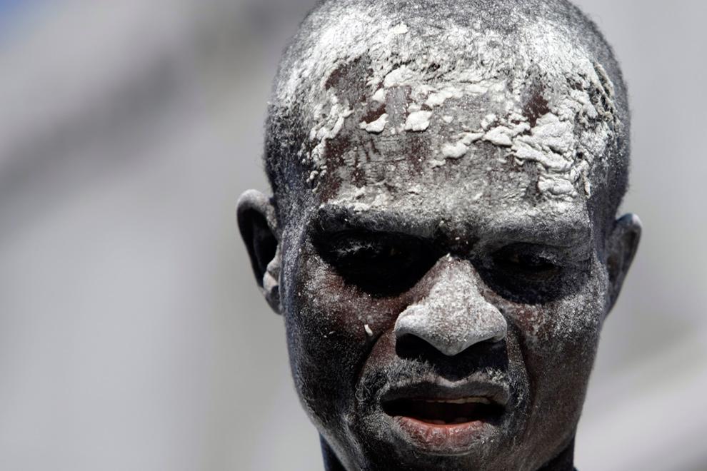 2. Лицо рабочего в муке во время разгрузки мешков с едой в Порт-о-Пренс 22 января 2010 года. Международная помощь, поступающая в Гаити после землетрясения 12 января, столкнулась с многочисленными проблемами, и многие люди все еще нуждаются в воде и еде. (AP Photo/Francois Mori)