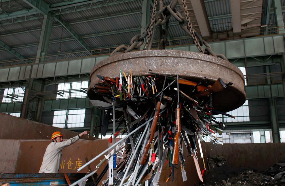 5. Рабочий готовится уничтожить конфискованное оружие на сталелитейном заводе в Шанхае 29 декабря 2009 года. Около 13 000 единиц нелегального оружия, пугачей, мачете и мечей, конфискованных полицией, были уничтожены во время специальной операции. (REUTERS/Aly Song)