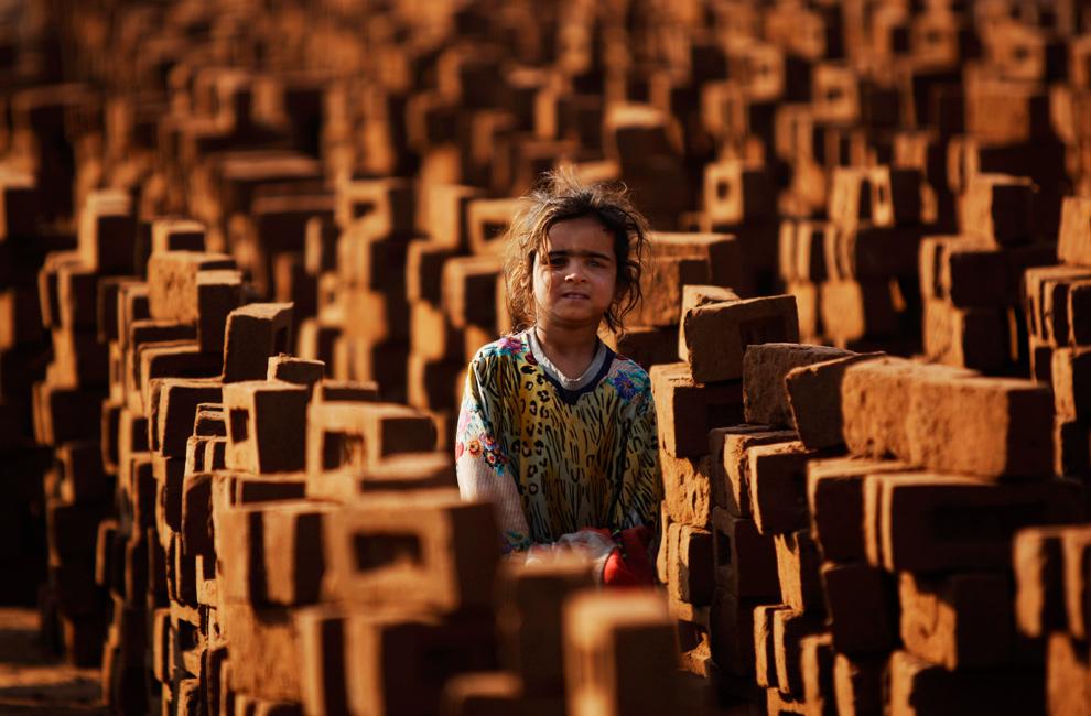 8. 7-летняя пакистанская девочка Кхалида Лали стоит между кирпичами, помогая своему отцу (нет на фото), на кирпичном заводе на окраине Исламабада 13 января 2010 года. (AP Photo/Muhammed Muheisen)