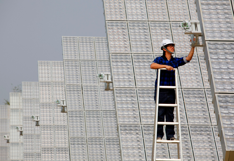 12. Рабочий проверяет панель на гелиостанции в районе Луйху округа Каосиунг в южном Тайване 22 января 2010 года. Это крупнейшая в Азии станция по производству электроэнергии с помощью солнца, тут установлены 141 панель и производится до 1 мегаватта энергии, благодаря чему, как заявляют власти, ежегодно предотвращает до 670 тонн выбросов углерода. (REUTERS/Nicky Loh)