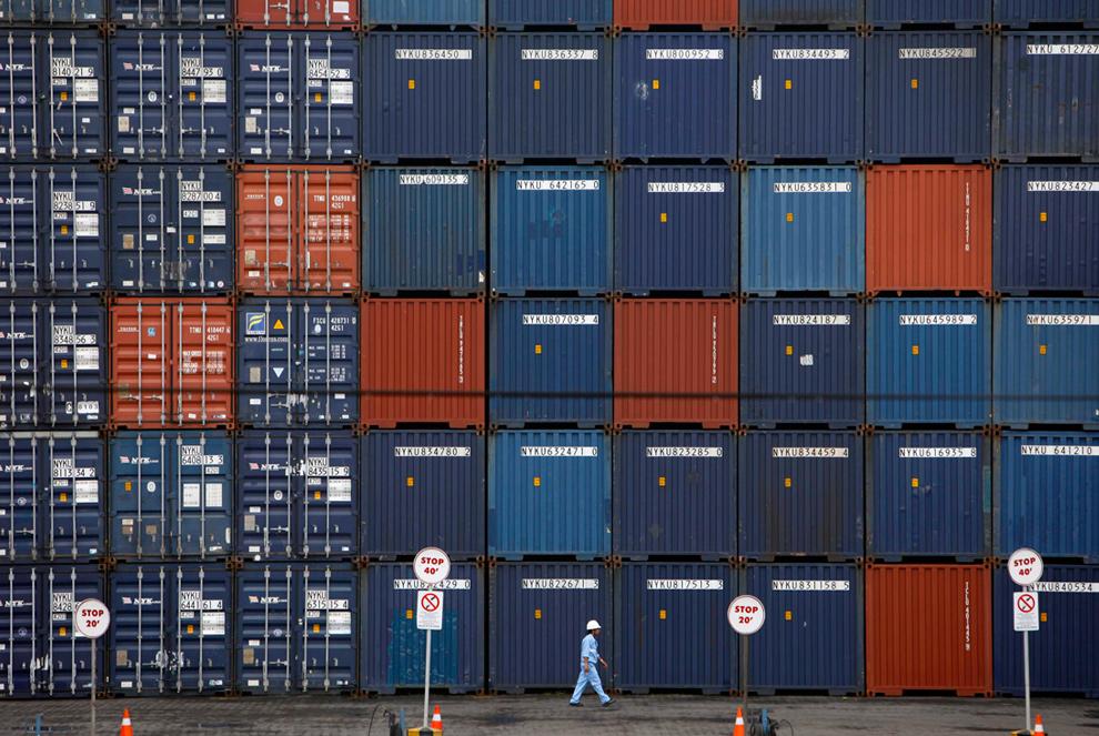 13. Рабочий проходит рядом с контейнерами в Международном контейнерном пункте Джакарты 13 января 2010 года. (REUTERS/Beawiharta)