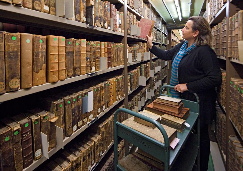 14. Работница библиотеки расставляет книги на полки в отделении древних рукописей муниципальной библиотеки Лиона 15 января 2010 года. В данный момент правительство Франции реализует проект по оцифровке содержимого библиотек и музеев Франции, который обойдется ему в 750 миллионов долларов. (REUTERS/Robert Pratta)