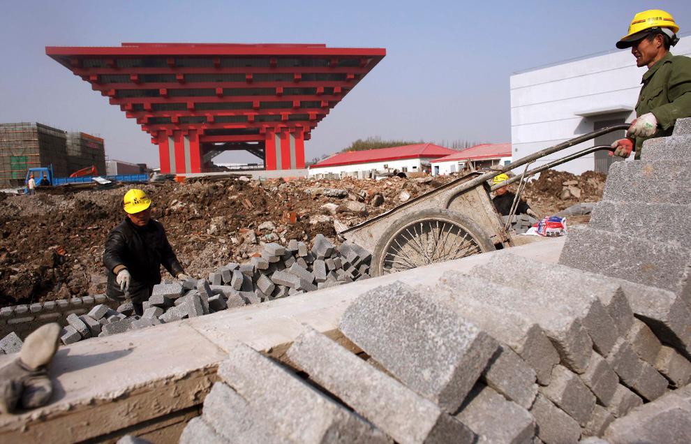 18. Строители-мигранты работают напротив китайского павильона на месте Всемирной выставки 2010 в Шанхае 6 января 2010 года. Выставка должна открыться 1 мая, и работа по строительству приближается к завершению. (REUTERS/Nir Elias)