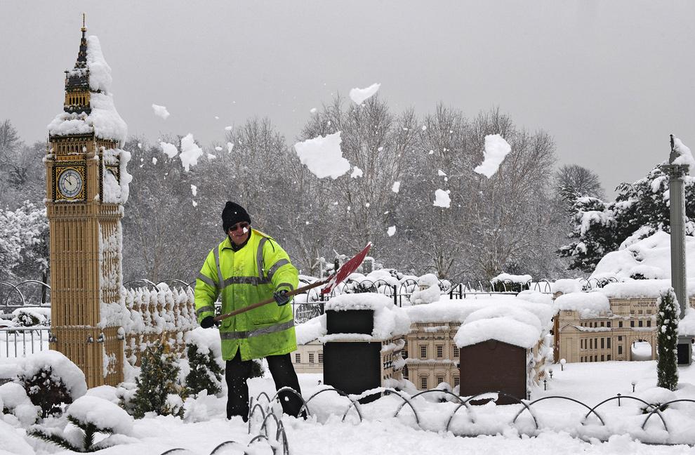 20. Работник «Леголенда» Грэм Уильямс убирает снег с моделей зданий, представляющих знаменитые достопримечательности Лондона – Биг Бен и Вестминстерское аббатство  - в Виндзоре, Беркшир, 6 января 2010 года. (CARL DE SOUZA/AFP/Getty Images)